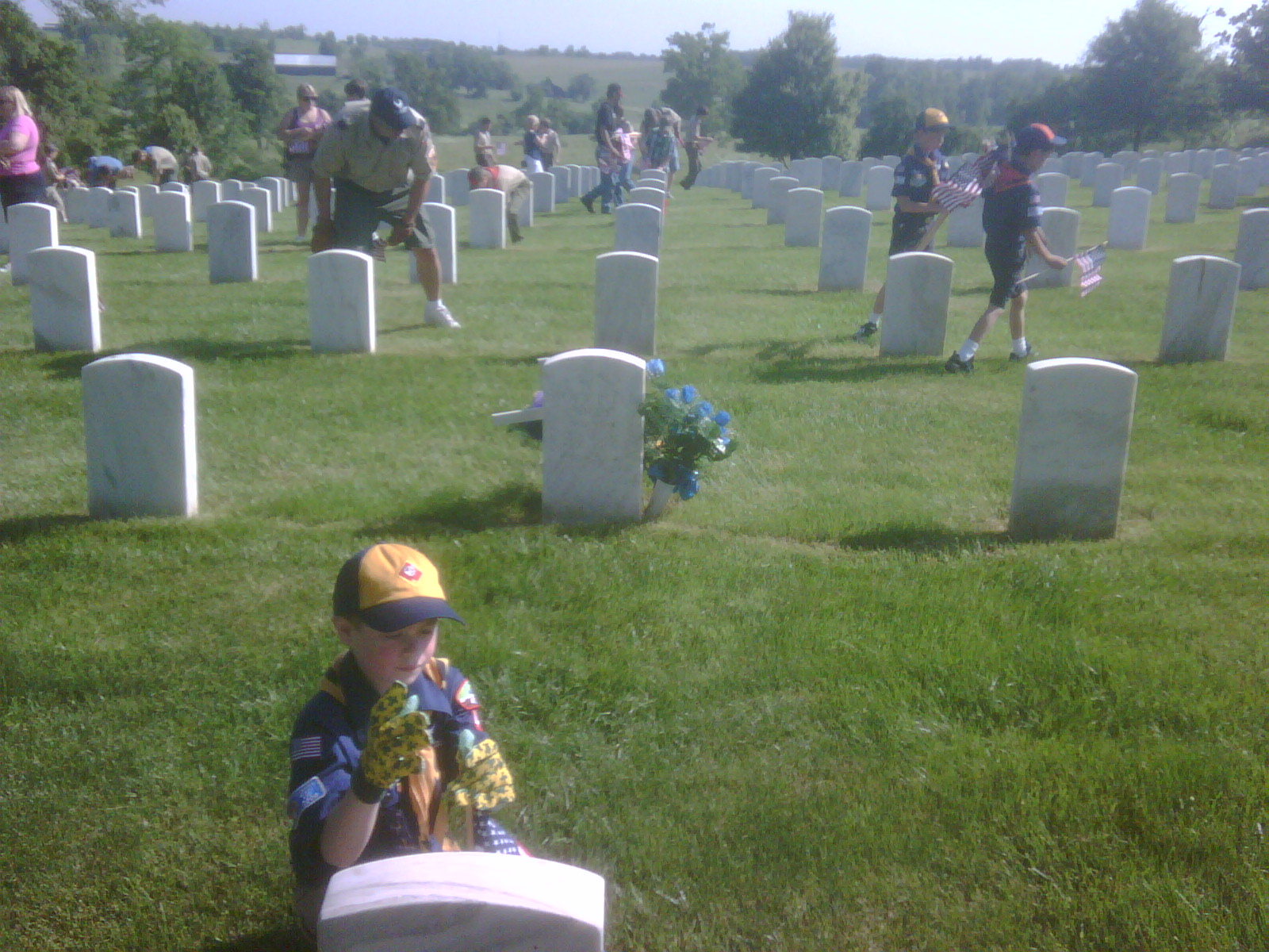 Colby placing a flag at one of the grave sites at Camp Nelson